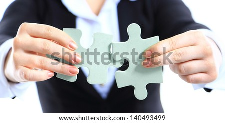 Business woman showing two jigsaw puzzle pieces . Concept for business strength and success. - stock photo