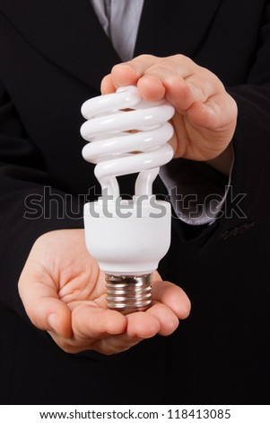 Business woman shows and holds economical lightbulb. - stock photo