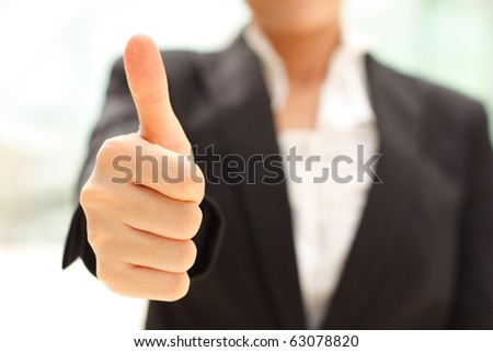 Business woman shows thumb up - stock photo