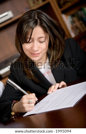 business woman signing a contract in her office - focus is on her right hand therefore text of the letter is not readable - stock photo