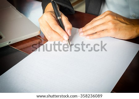 Business woman signing a contract.Vintage tone,Retro filter effect,Soft focus,Low light.(selective focus) - stock photo