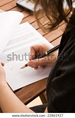 Business woman signing a contract with a fountain pen