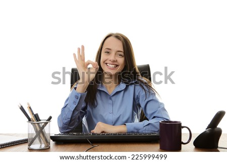 business woman sitting at her desk doing a ok sign with her hand - stock photo