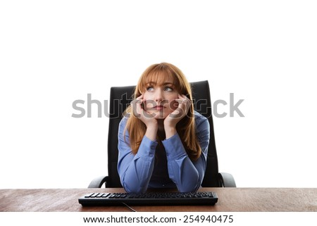 business woman sitting at her desk not looking very happy - stock photo