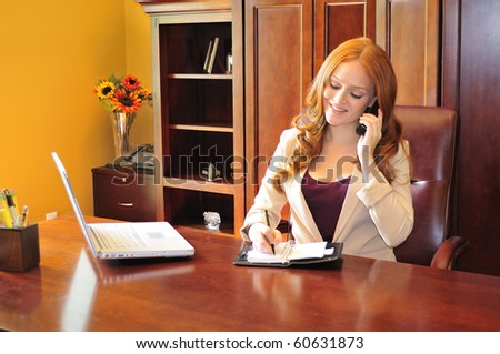 business woman sitting at her office desk and writing a message in her organizer - stock photo
