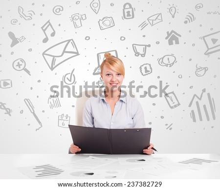 Business woman sitting at table with hand drawn media icons and symbols - stock photo