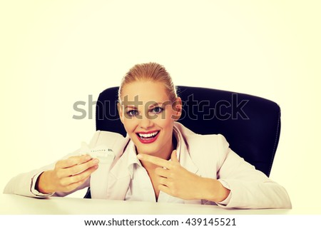 Business woman sitting behind the desk and holding a toy plane - stock photo