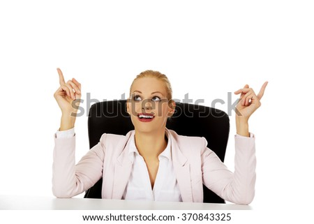 Business woman sitting behind the desk and pointing up for copyspace or something  - stock photo