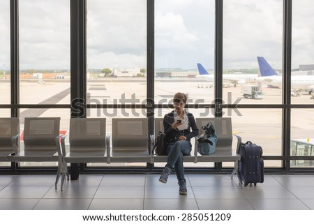 Business woman sitting in airport terminal with suitcase and waiting for departure while using mobile phone. Concept of people sharing informations with new technology while traveling. - stock photo