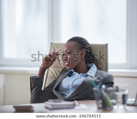 Business woman sitting in armchair at office and planning - stock photo