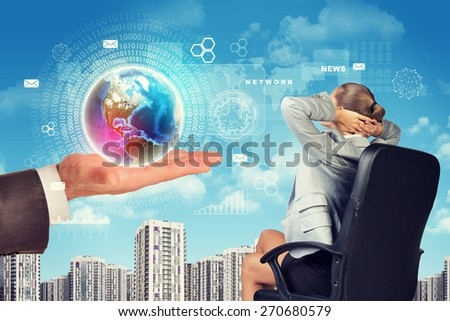 Business woman sitting in chair and right hand of businessman holding globe. World on hand. Elements of this image furnished by NASA - stock photo