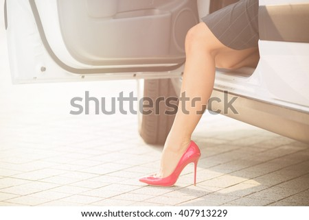 Business woman sitting in her car. She is going to get out from the car. Slim and slender woman's leg on high heels looking from the car. Toned image. - stock photo
