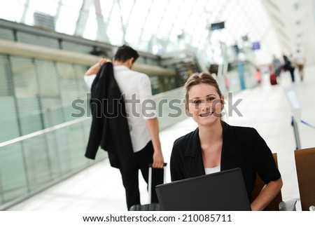 business woman sitting in public station and working with a computer in wifi area - stock photo