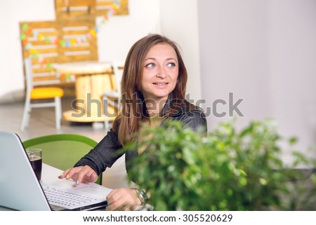 Business woman sitting in the office and working using a laptop ps. Young businesswoman sitting at desk and working. Business woman using laptop computer. - stock photo