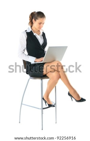 Business woman sitting on a high chair and works on the laptop. Isolated on white. - stock photo