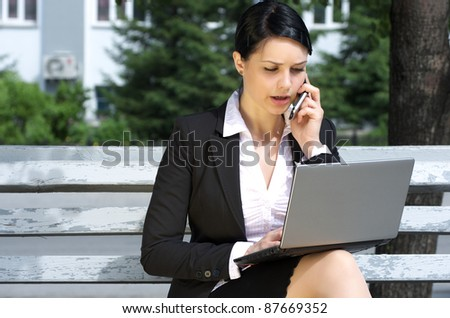 Business woman sitting on bench in park and working on laptop - stock photo