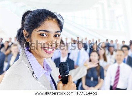 Business woman smiling at the front of the other business persons - stock photo
