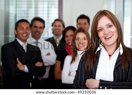 Business woman smiling at the office with her team