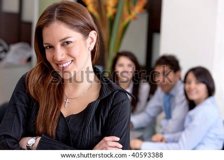 Business woman smiling in an office with her team behind her
