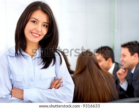 business woman smiling leading a team during an office meeting - stock photo