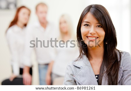 Business woman smiling with a group behind her