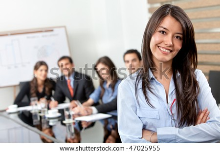 Business woman smiling with her team behind her