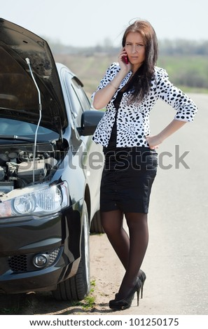 Business woman speaking by mobile near  her broken car - stock photo