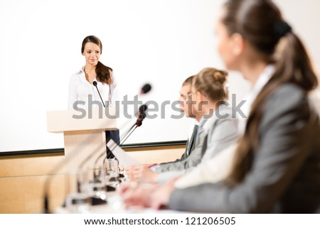 Business woman speaks into a microphone, communication businessmen at a conference