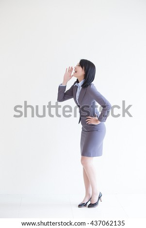business woman stand and shout to copy space with white wall background, great for your design or text, asian