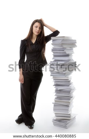 business woman standing against a large pile of paper work not looking very happy