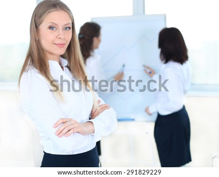 Business woman standing in foreground and her co-workers discussing business matters in the background - stock photo