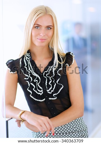 Business woman standing in foreground  in office - stock photo