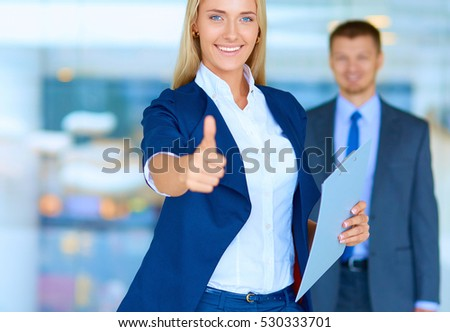 Business woman standing in foreground , showing ok