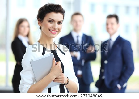 Business woman standing in foreground with a tablet in her hands, her co-workers discussing business matters in the background - stock photo