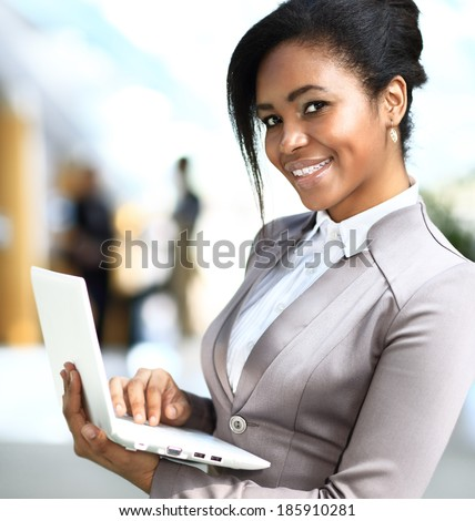 Business woman standing in foreground with laptop in her hands, her co-workers discussing business matters in the background, tilt up