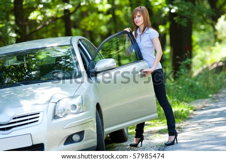 Business woman standing near by her car in a forest