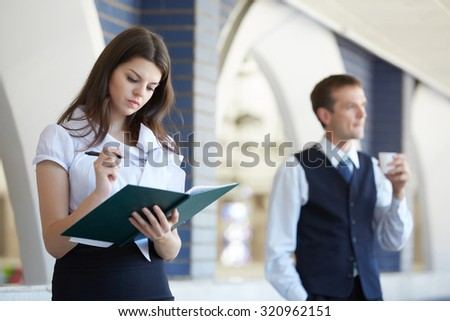 Business woman standing with a notebook, a businessman walking down the corridor - stock photo