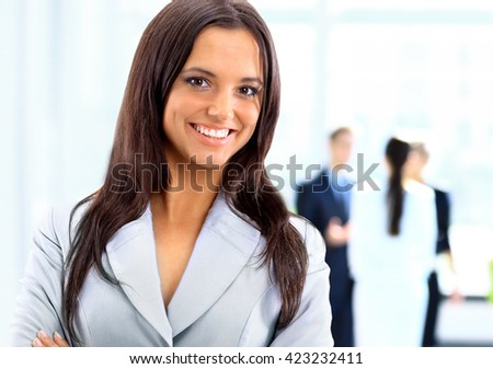 business woman standing with her staff in background at office - stock photo