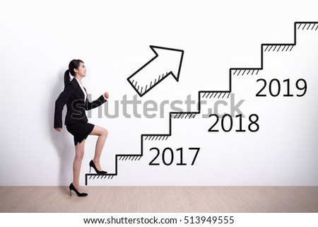 Business woman stepping up on stairs to gain her success in 2017 new year