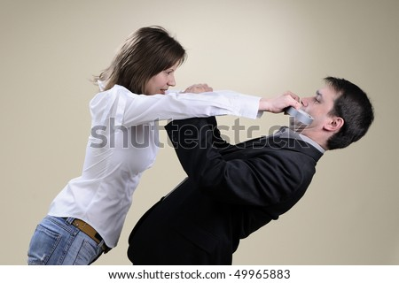 business woman sticking her colleague mouth - stock photo