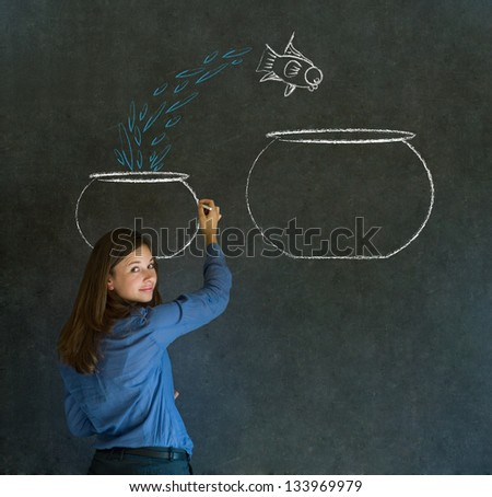 Business woman, student or teacher with fish jumping from small bowl to big bowl on blackboard background - stock photo