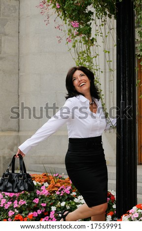 Business Woman Swinging On A Lam Post In The City - stock photo