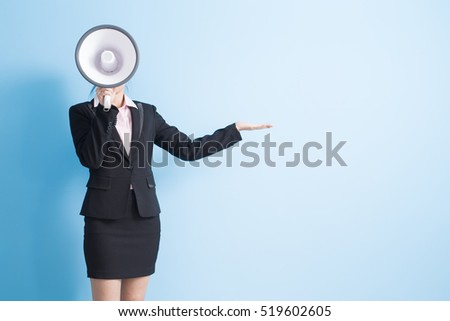 business woman take microphone and show something ,isolated blue background