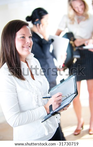 Business woman taking notes with colleagues in background