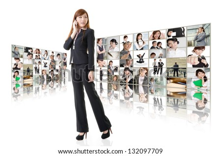 Business woman talk on cellphone in front of video wall. Business conferencing and global communications concept. - stock photo