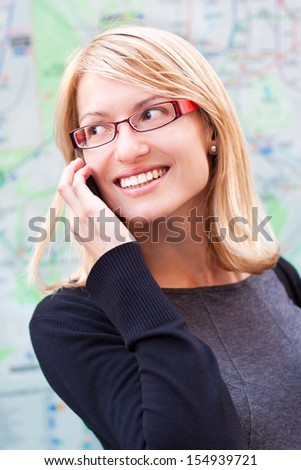Business woman talking by cell phone in front of the metro map. - stock photo