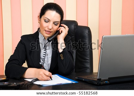 Business woman talking by phone and writing on papers in her office - stock photo