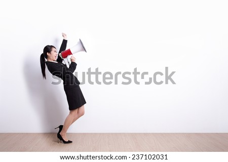 business woman talking in megaphone with white wall background, great for your design or text, asian - stock photo