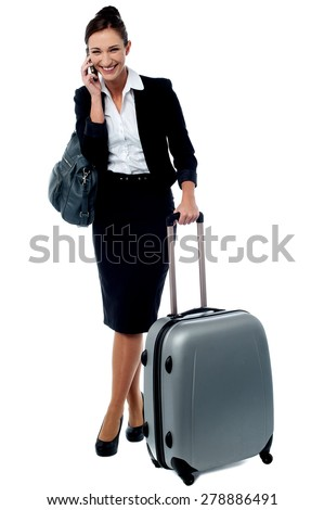 Business woman talking on cell phone with luggage - stock photo