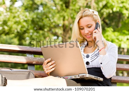 Business Woman talking on phone and looking at laptop